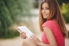 Beautiful young woman using tablet pc outdoor. Stock Photography