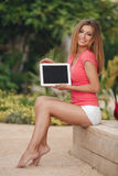 Beautiful young woman using tablet pc outdoor. Royalty Free Stock Photo