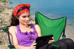 Beautiful young woman using a tablet in vacation Royalty Free Stock Images