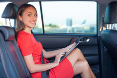 Beautiful young woman is using a tablet in vehicle Royalty Free Stock Photo