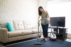 Pretty young woman cleaning her house. Beautiful young woman is using a vacuum cleaner and smiling while cleaning her house Stock Image