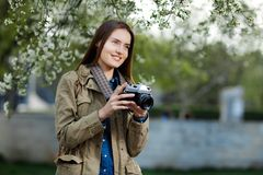 Beautiful young woman using vintage photo camera in the park. Beautiful young woman using vintage photo camera in the park Royalty Free Stock Photos