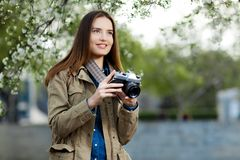 Beautiful young woman using vintage photo camera in the park. Beautiful young woman using vintage photo camera in the park Stock Photography