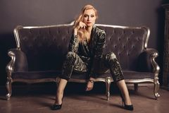 Beautiful young woman in a velor suit sits on a gray vintage couch.  Royalty Free Stock Images