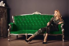 Beautiful young woman in a velor suit sits on a green vintage couch.  Stock Photography
