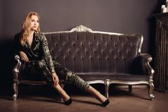 Beautiful young woman in a velor suit sits on a vintage sofa.  Stock Photos