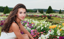Beautiful Young Woman in Versailles. Beautiful young woman in a fashion/lifestyle pose in the gardens of the Palace of Versailles in Paris, France stock photo