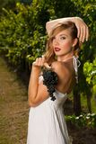 Beautiful young woman in vineyard holding a grape Stock Image