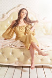 Beautiful young woman on vintage bad. Beautiful young woman in golden dress sitting on vintage bad Royalty Free Stock Photo