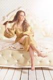Beautiful young woman on vintage bad. Beautiful young woman in golden dress sitting on vintage bad Stock Image