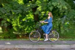 Beautiful young woman and vintage bicycle, summer. Red hair girl riding the old black retro bike outside in the park. Royalty Free Stock Photography