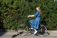 Beautiful young woman and vintage bicycle, summer. Red hair girl riding the old black retro bike outside in the park. Royalty Free Stock Images