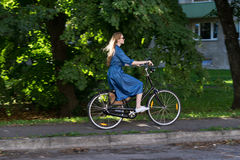 Beautiful young woman and vintage bicycle, summer. Red hair girl riding the old black retro bike outside in the park. Stock Image