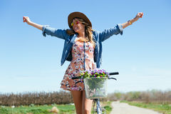 Beautiful young woman with a vintage bike in the field. Stock Photos