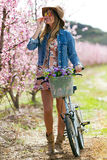 Beautiful young woman with a vintage bike in the field. Royalty Free Stock Photo