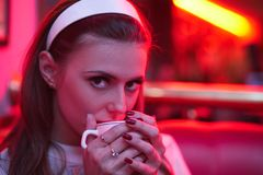 Beautiful young woman in vintage dress in red light cafe drinking coffee. Beautiful young woman with rim on head in vintage dress in red light cafe drinking Royalty Free Stock Image