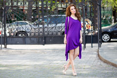 Beautiful young woman with violet dress Royalty Free Stock Images