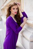 Beautiful young woman with violet dress Royalty Free Stock Photography