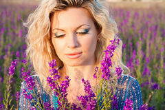 Beautiful young woman in violet flowers Stock Images
