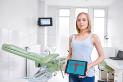Beautiful young woman visiting doctor. Attractive young woman standing in the gynecological room at the hospital smiling to the camera holding digital tablet Royalty Free Stock Photography