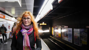 Beautiful young woman waiting subway at underground - train arrives. Wide angle Stock Photos