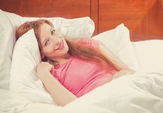 Beautiful young woman waking up in bed at home Royalty Free Stock Photography