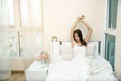 Beautiful young woman waking up after a night sleep. Girl stretching after wake up.  stock photography