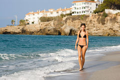 Beautiful young woman walking. On the beach Royalty Free Stock Photos