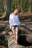 Beautiful young woman walking across a log over creek Stock Photo