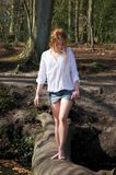Beautiful young woman walking across a log over stream Royalty Free Stock Photo