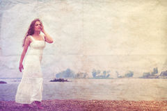 Beautiful Young Woman Walking along the Beach in White Dress. Royalty Free Stock Photos