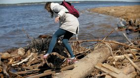 Beautiful young woman walking along the river bank and collecting dry branches. 4k stock video footage