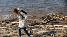 Beautiful young woman walking along the river bank and collecting dry branches. 4k stock video