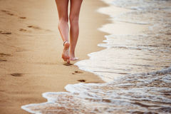 Beautiful young woman is walking along seashore leaving footprints Royalty Free Stock Photography