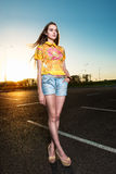Beautiful young woman walking on asphalt road Stock Images