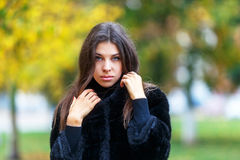 Beautiful young woman walking in autumn park. Autumn fashin concept. Royalty Free Stock Photos