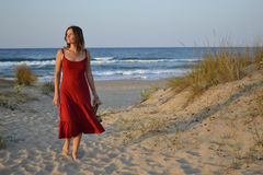Beautiful young woman walking back from the beach Royalty Free Stock Image