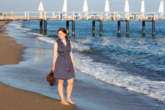 Beautiful young woman walking on the beach enjoying the sun Royalty Free Stock Photos