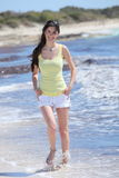 Beautiful young woman walking on the beach Royalty Free Stock Photography