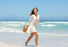 Beautiful young woman walking on beach in summer dress Royalty Free Stock Photography