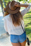 Beautiful young woman walking with her dog in the park. Royalty Free Stock Images