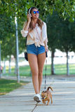 Beautiful young woman walking with her dog in the park. Royalty Free Stock Photos