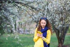 Beautiful young woman walking in the lush spring garden Stock Image
