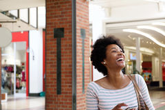 Beautiful young woman walking in mall with mobile phone Stock Photography