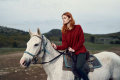 Beautiful young woman walking in the mountains with her horse Royalty Free Stock Images