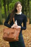 Beautiful young woman walking outdoors with bag on an autumn day Stock Photo