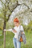 Beautiful young woman walking outside in a field, looking at her cell phone royalty free stock photo