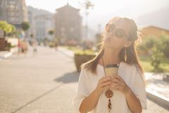 Beautiful young woman walking with paper cup. royalty free stock photos