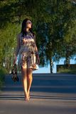 Beautiful young woman walking in the park Stock Photography