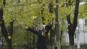 Beautiful young woman walking in a park, throwing up autumn maple leaves stock video footage